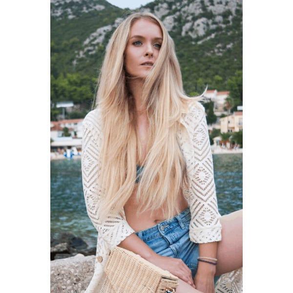 hosszú szőke hajú lány ül a tengerparton