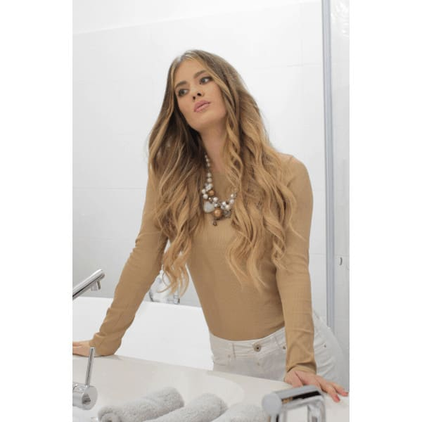 wavy blonde haired girl looking at herself in the mirror