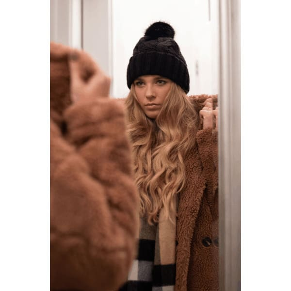blonde wavy haired girl with a black beanie