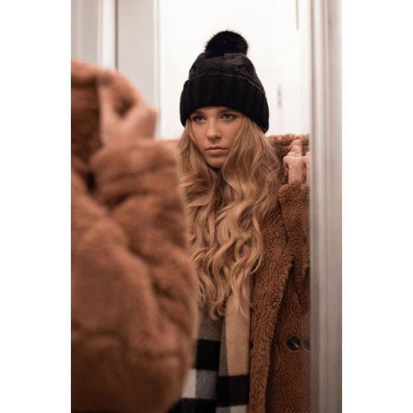 szőke göndör hajú lány fekete sapkában cuki kabátban