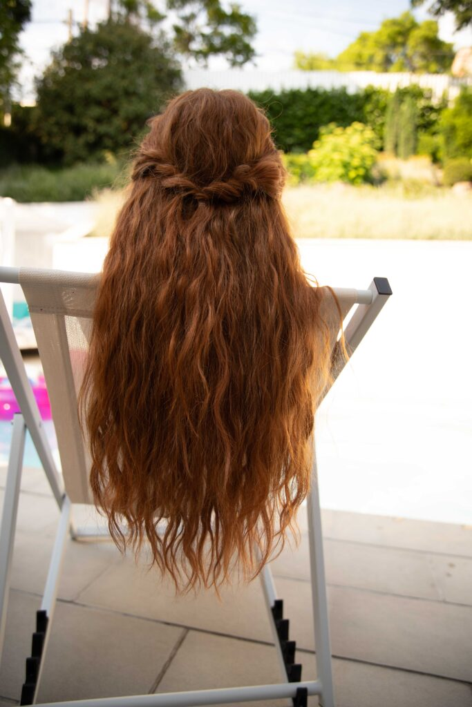 ginger haired girl by the pool in the summer