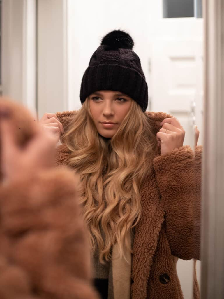blonde girl with wavy hair wearing a beanie